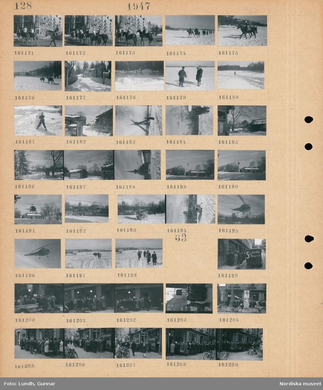"""Motiv: (ingen anteckning) ; Stadsvy med kvinnor och män som rider till häst, snötäckt landskapsvy med två kvinnor som rider till häs och fotgängare, exteriör av hus, en isfiskare, ett barn gör en snögubbe, en helikopter flyger över hus, en helikopter landar på snön.  Motiv: (ingen anteckning) ; Kvinnor och män står i kö på en trottoar utanför en byggnad, en skåpbil med text """"Stockholms Bageri a.b.""""."""