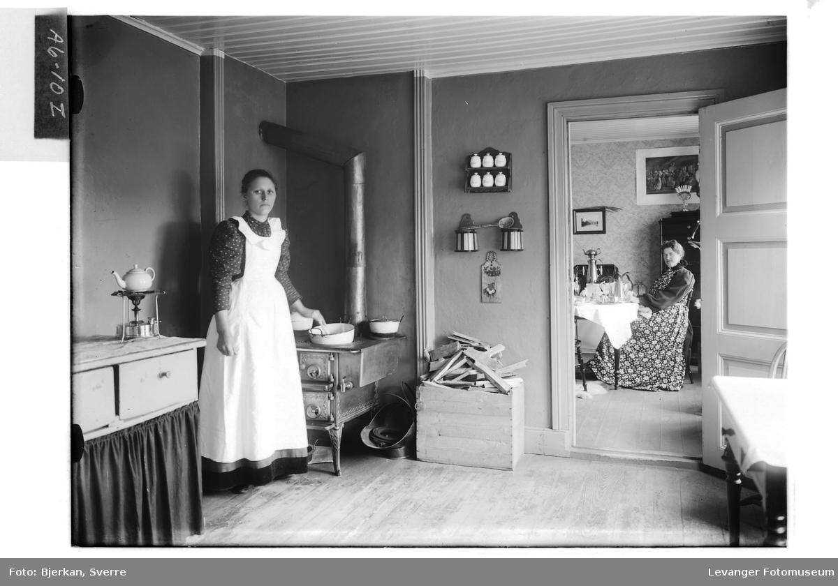 På  kjøkkenet hushjelpa  i forgrunnen, mens frua sitter inne på stua.