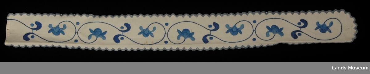 Til å ha rundt ostestykke. Brodert med blått brodergarn på hvitt linstoff, blå tunget kant rundt ene langsiden og endestykket (avrundet) Andre endestykket rett. Mønsker, blomsterbord med slyngede stilker.