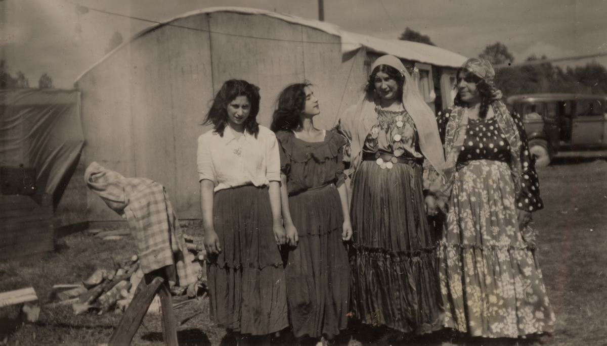 Två flickor och två kvinnor framför ett tält och en bil. Under sommaren 1947 bodde romer i ett läger i Sandviken. Fotografiet är taget i juni detta år. I bakgrunden syns eldstaden i lägret.