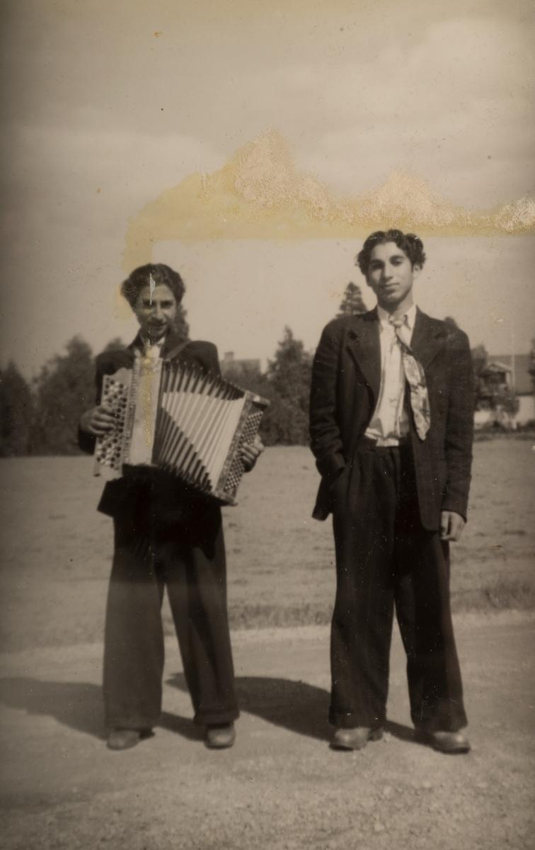 Två romska pojkar, en håller i ett dragspel. Det är känt att romer bodde i ett läger i Sandviken under sommaren 1947. Fotografiet är taget i juni detta år.