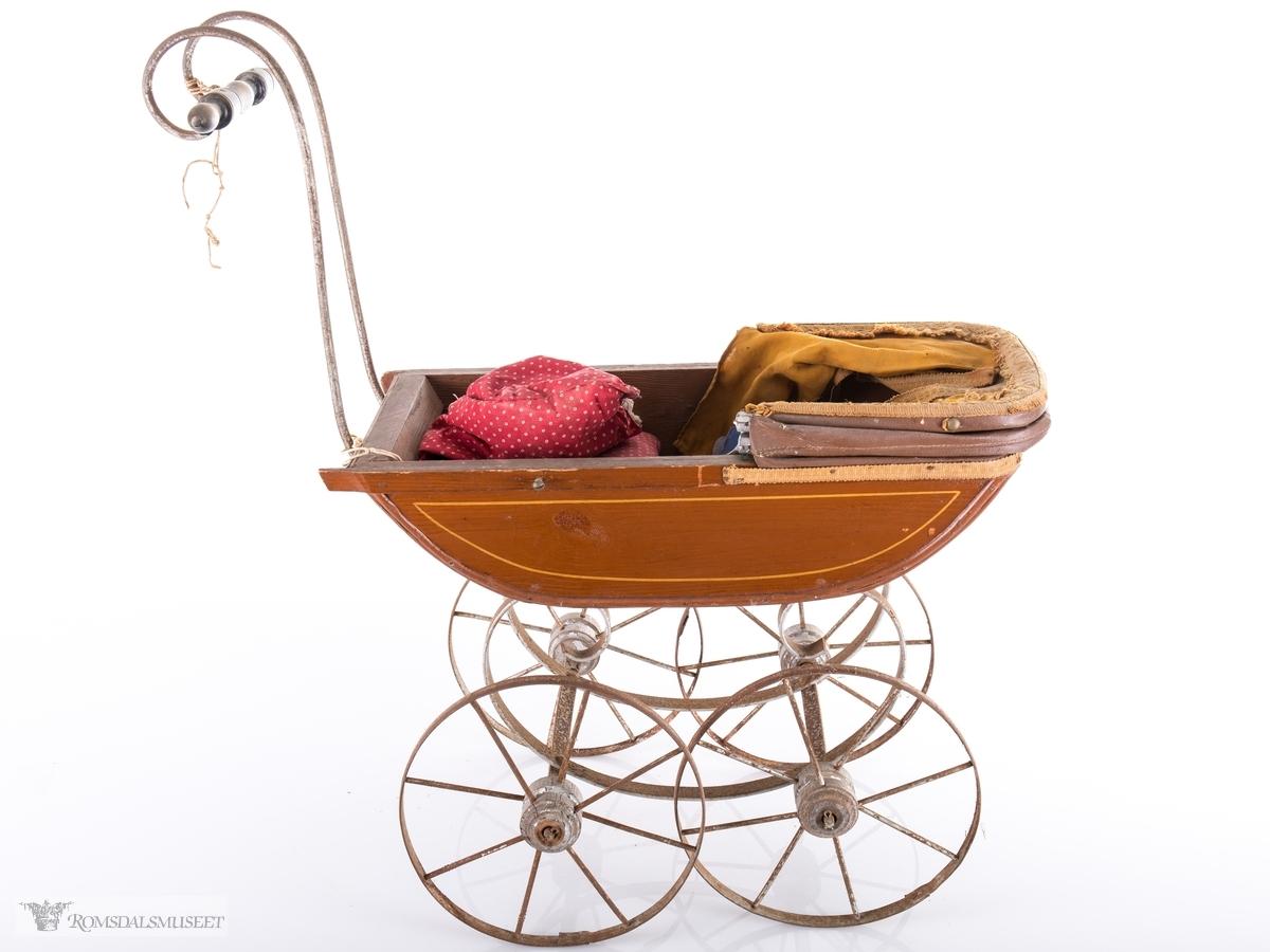 Dukkevogn i tre med metallunderstell og kalesje. En liten plastdukke med klær og pute og dyne følger med.