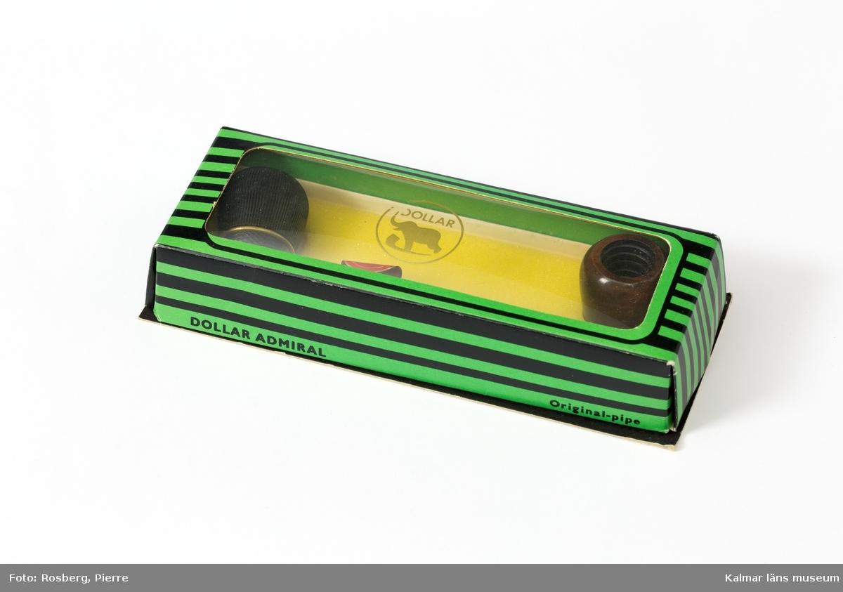 KLM 45058:5:1-3. Pipa i originalförpackning. Pipa av trädljung/briar, förpackning av papp. :5:1 Pipa med rakt, svart munstycke. Det rundade piphuvudets överdel har ett räfflat mönster och den nedre delen ett rombiskt mönster. De skiljs åt av en gul metallring. :5:2 Piphuvud, extra, brunt, polerat, rundat piphuvud. :5:3 Förpackning, randig i grönt och svart med locket delvis av plast. Texten Dollar och en bild av en elefant som står på en pipa tryckt på plasten. Askens botten fodrad invändigt med skumgummi.