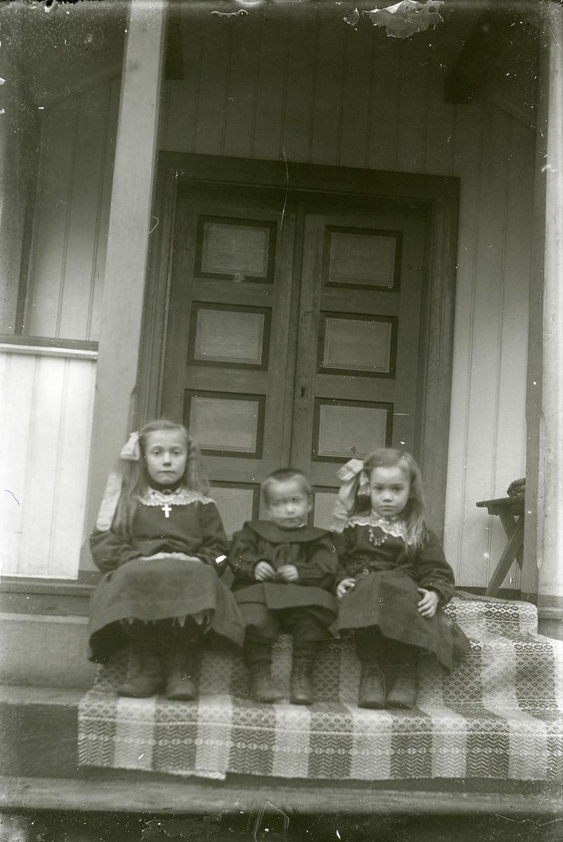 Tre barn sit på ei trapp.