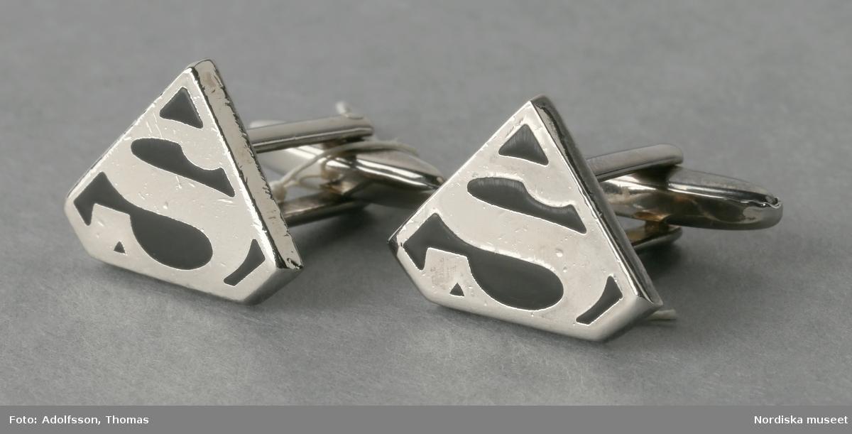 """Ett par manschettknappar av vitmetall. Trekantig ovandel med två avskurna hörn. Ovandelen med ett S i silver mot svart botten.  Undertill fästanordning bestående av två smala metalltenar med rörlig metallten nertill (för att """"låsa"""" knappen i manschetten"""").  Undertill på den trekantiga knappen, präglat """"T.M©D.C."""" /Leif Wallin 2015-08-11"""