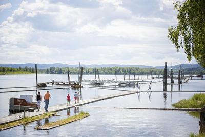 Foto av fløtingsanlegget. Flere personer går på flåter i vannet.