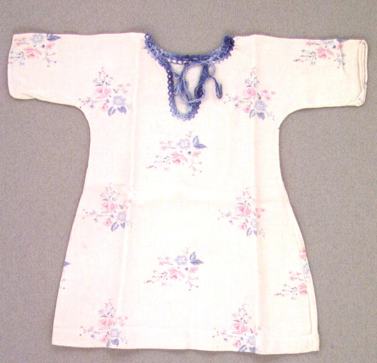 Docksärk av ljusrosa bomullstyg med tryckt blommotiv i rosa och blått. Rundhalsad med sprund, laskade kanter i blåmelerat bomullsgarn.