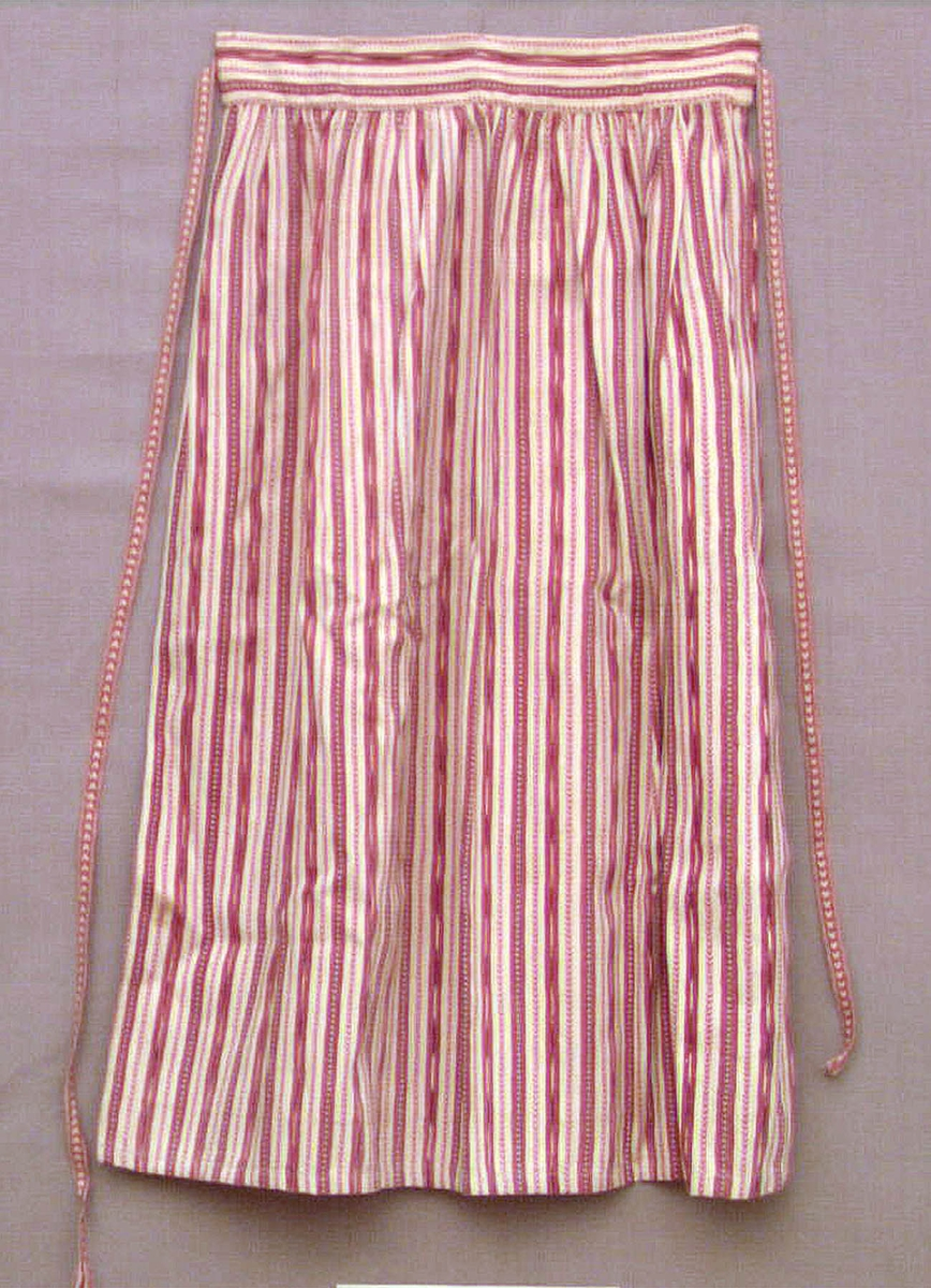 """Förkläde av bomullstyg. Vit botten i tuskaft med inslag av smala ränder i rött och blått. Handvävt tyg. Försett med linning mot vilken förklädet är rynkat. Försett med handvävda bomullsband, s k """"hjärtband"""". Förklädet är både maskin- och handsytt. Förmodligen tillverkat i modern tid.  Ett s k """"kvistaförkläde"""" från Ovansjö socken, använt som sommarförkläde för ogift kvinna i kyrkan."""