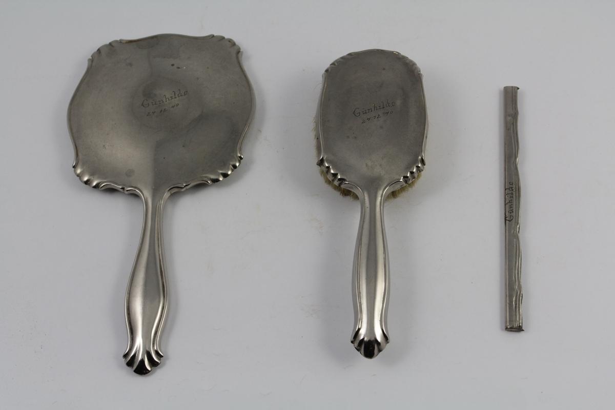 Sett med speil, børste og ramme til kam. Formet og rundet. Speil og hårbørste med håndtak. Gravert tekst.