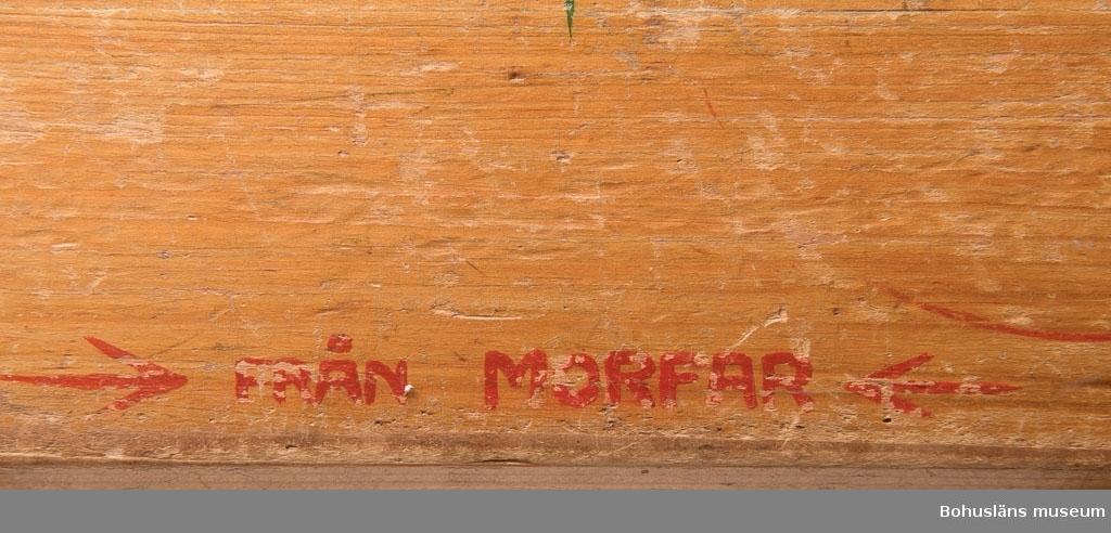 """Barnpall i furu; lackad. Sits med handtagshål i mitten, utmed långsidorna kantbräda på vardera sidan, försedda med målade stiliserade gröna blommor och på ena sidan texten: """"Gunda 1941"""" och på andra: """"Från morfar"""". All text i rött. På sitsens undersida i blyerts """"J.A. Grundberg"""". Slitage. Släkt- och personuppgifter se UM026024"""