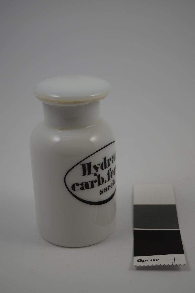 Porselenskrukke med propp. Sort oval etikett påført på krukken. Til oppbevaring av legemidler/pulver. Stoffet i krukken ble brukt til blant annet jernpreparat.