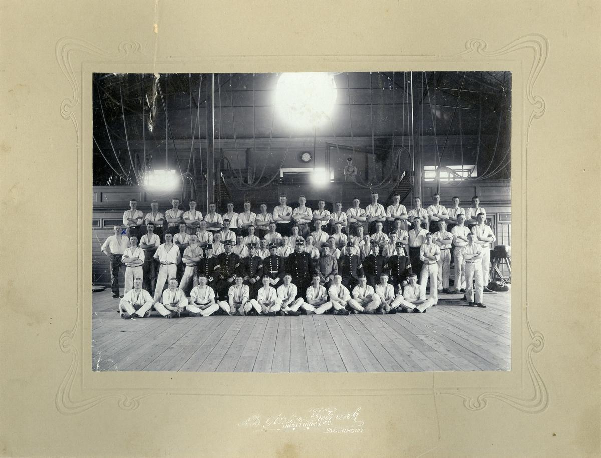 Grupporträtt av officerare och soldater i gymnastiksal.
