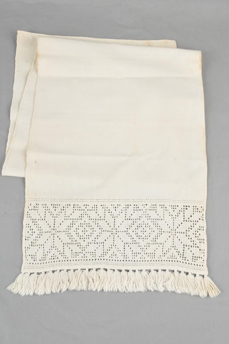 Rektangulært klede av lin- eller bomullslerret, til bruk på grautspann. Utsauma bord med åttebladroser i dobbel uttrekkssaum på eine kortsida. Austmannarenning på kvar side av denne. Frynser av bomullsgarn i enden. Smal fald sydd til med faldesting.