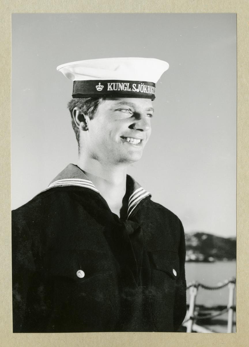 Bilden föreställer Carl XVI Gustaf klädd i mörk uniform. Bilden är tagen under minfartyget Älvsnabbens långresa 1966-1967.
