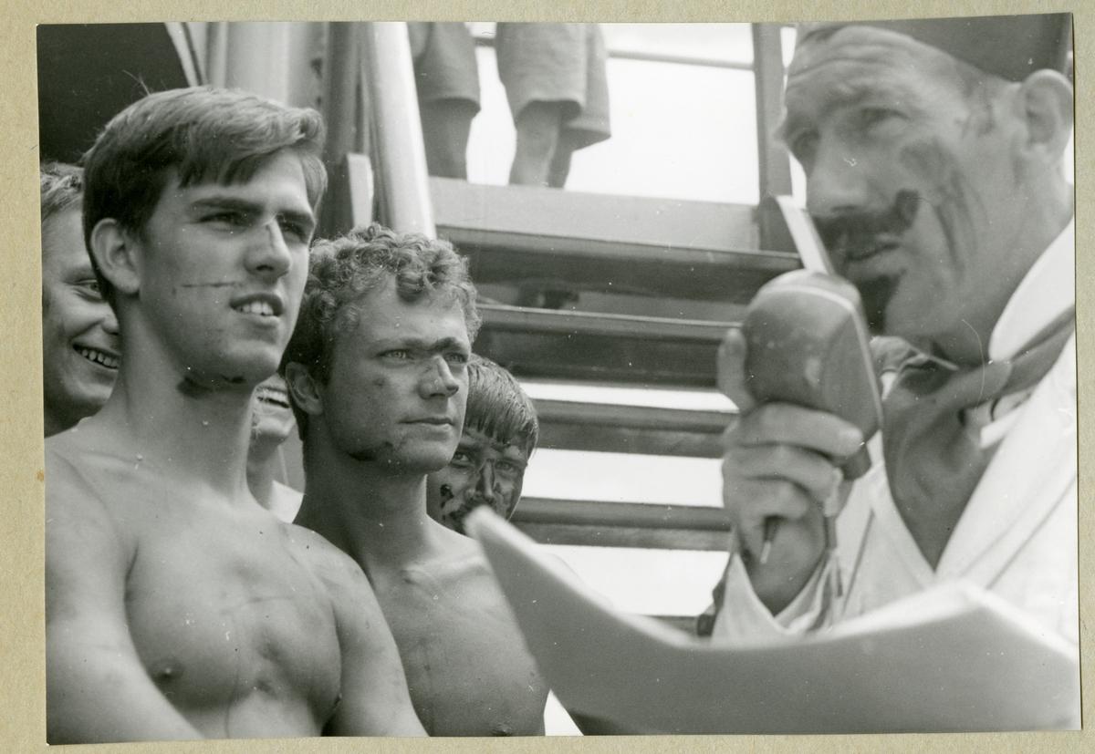 Bilden föreställer besättningsmän ombord på minfartyget Älvsnabben under ceremonierna kring ett linjedop. På bilden syns bland annat kronprinsen Carl Gustav, den senare kung Carl XVI Gustaf, som stå och lyssna till Oskar Linde som är utklädd till Neptuns sekreterare och talar i en mikrofon. Bredvid kronprinsen, till vänster på bilden, står aspirant Hans-Eric von der Groeben.