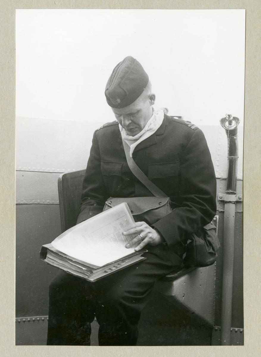 Bilden föreställer Älvsnabbens SigO (signaltjänstofficer), löjtnant Sten Swedlund, som sitter med en pärm med papper i knät ombord på minfartyget Älvsnabben under långresan 1966-1967.