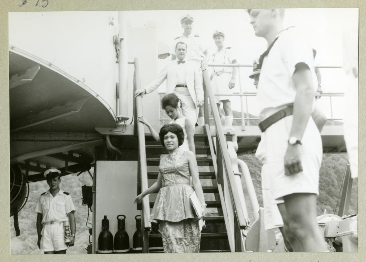 Bilden visar två fin klädda damer som går ner en trappa på örlogsfartyget Älvsnabben. De svenska sjömän i sceneriet står i giv akt. Enligt uppgifter från ett besättningsmedlem är det en prinsessan från Tonga som besökte det svenska minfartyget under sin långresa 19966/67.