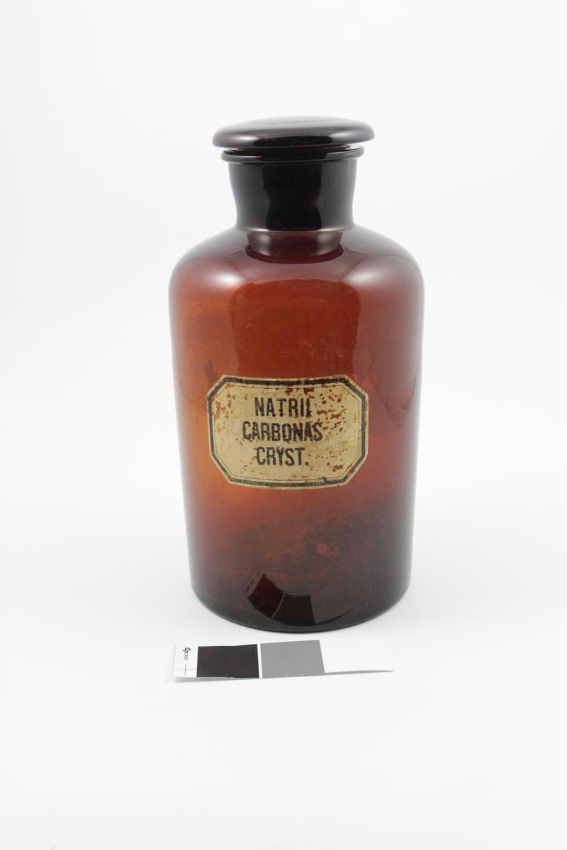 Brunt standglass med vid hals og glasspropp. Hvit etikett med sort skrift. Brukt til oppbevaring av pulver.
