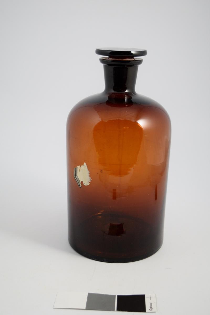 Brun glassflaske, smal hals, brun glasspropp. Brukt til oppbevaring av løsninger eller løsemidler.