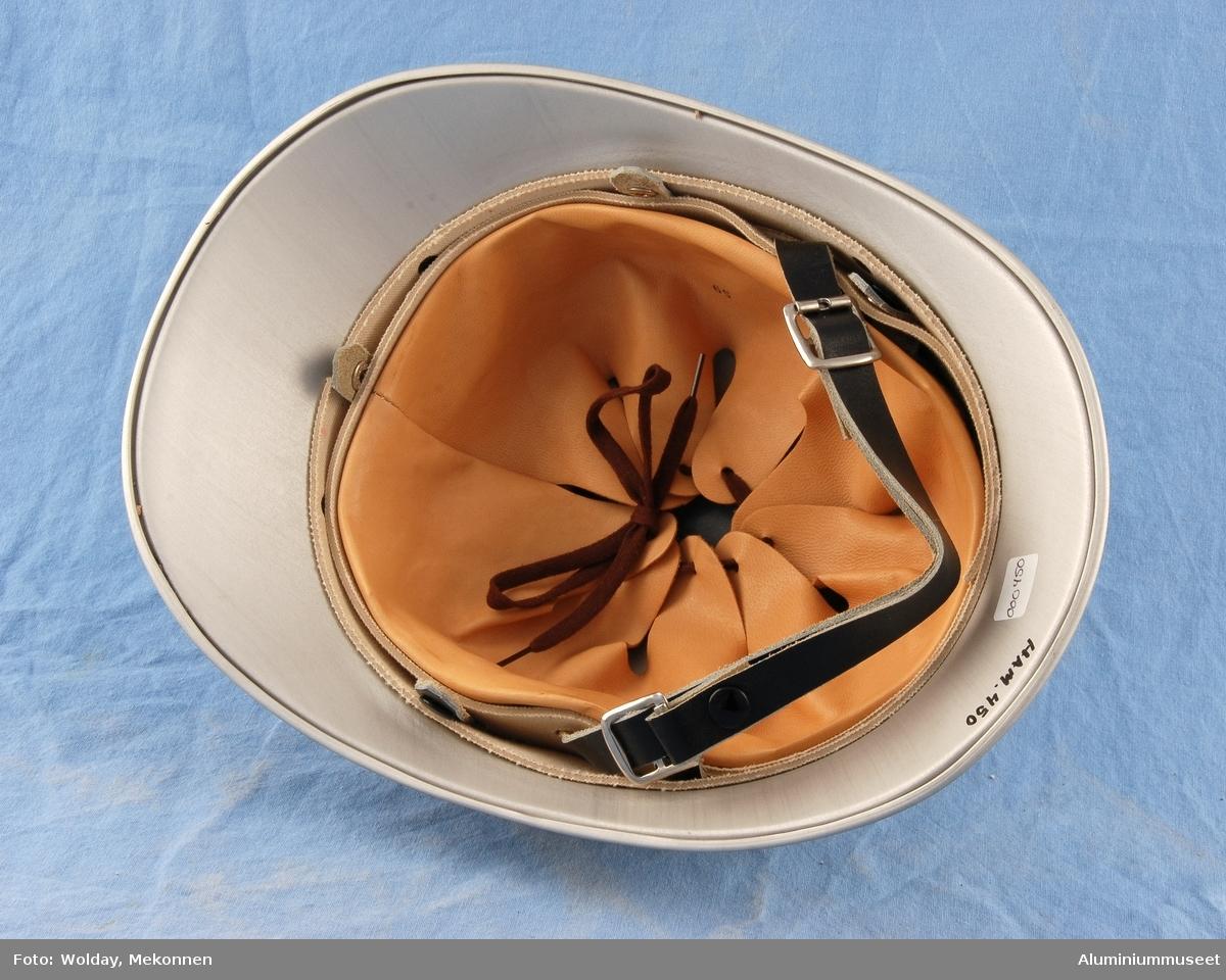 Teknikk: Hjelmen er trykket i hatteprofilet, men i rund utførelse. Hjelmen er  presset til oval form. Hjelmen er så renskåret og falset før eloksering. Kammen er presset i to halvdeler. den er sveiset og renskåret før eloksering. Etter eloksering ble hjelmen boret og montert på blikkenslagerverkstedet. Form: Rund, oval form, med kam str.59