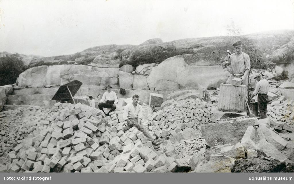Fyra stenhuggare står omgivna av gatsten och bearbetar densamma