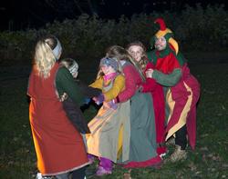 Fem barn i middelalderklær får hjelp av en narr til tautrekking. (Foto/Photo)