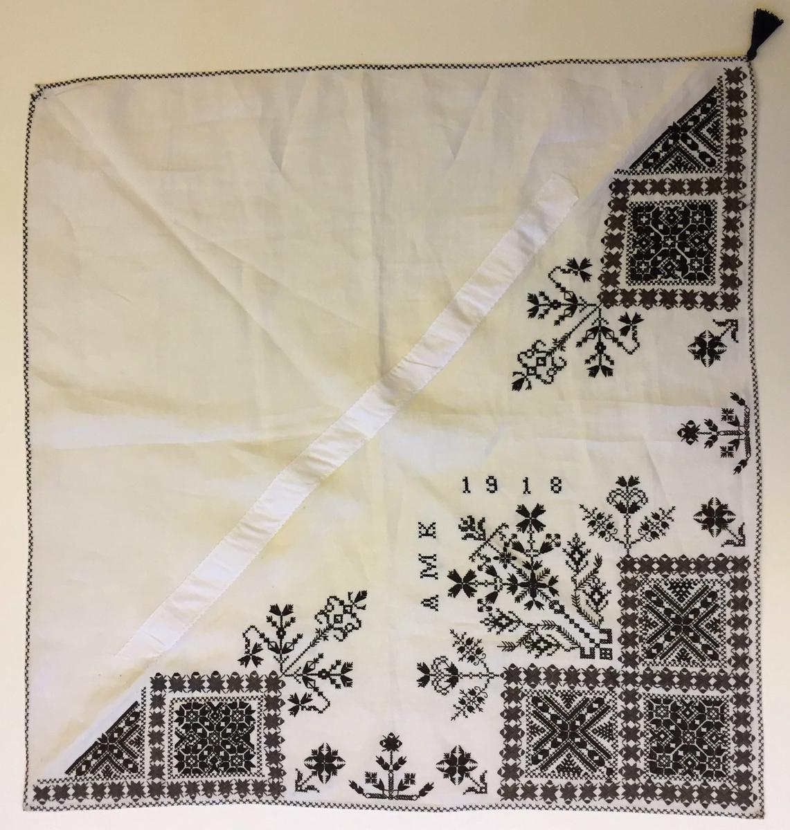 Kvadrater omgivna av blomsterliknande bård. I kvadraterna blomsterliknande geografiskt mönster, rikt dekorerad majstångsspira mellan kvadraterna blomsterliknande motiv.