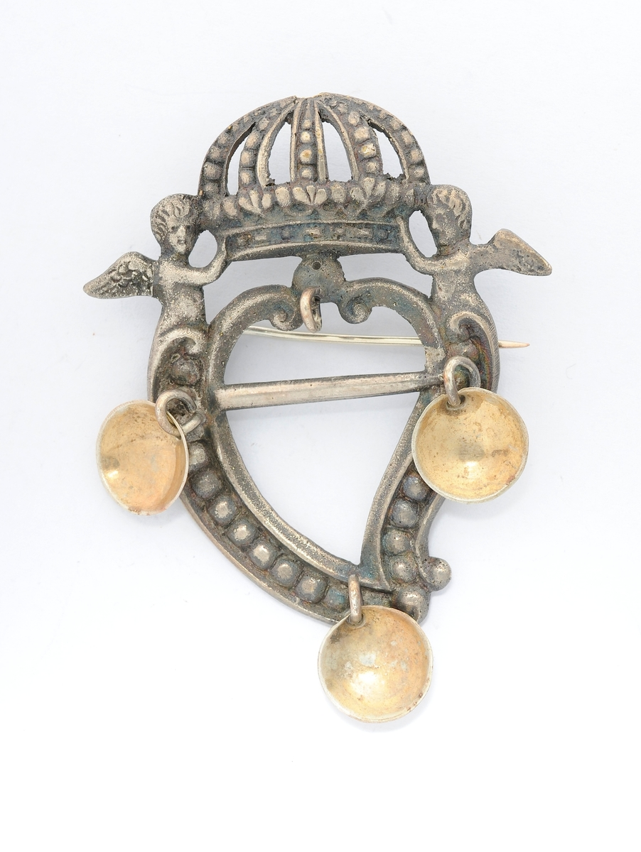 Sølje i sølv? Støypt med eit hjarte på midten og med ein engel på kvar side som held ei krone. Tre forgylte skåler.