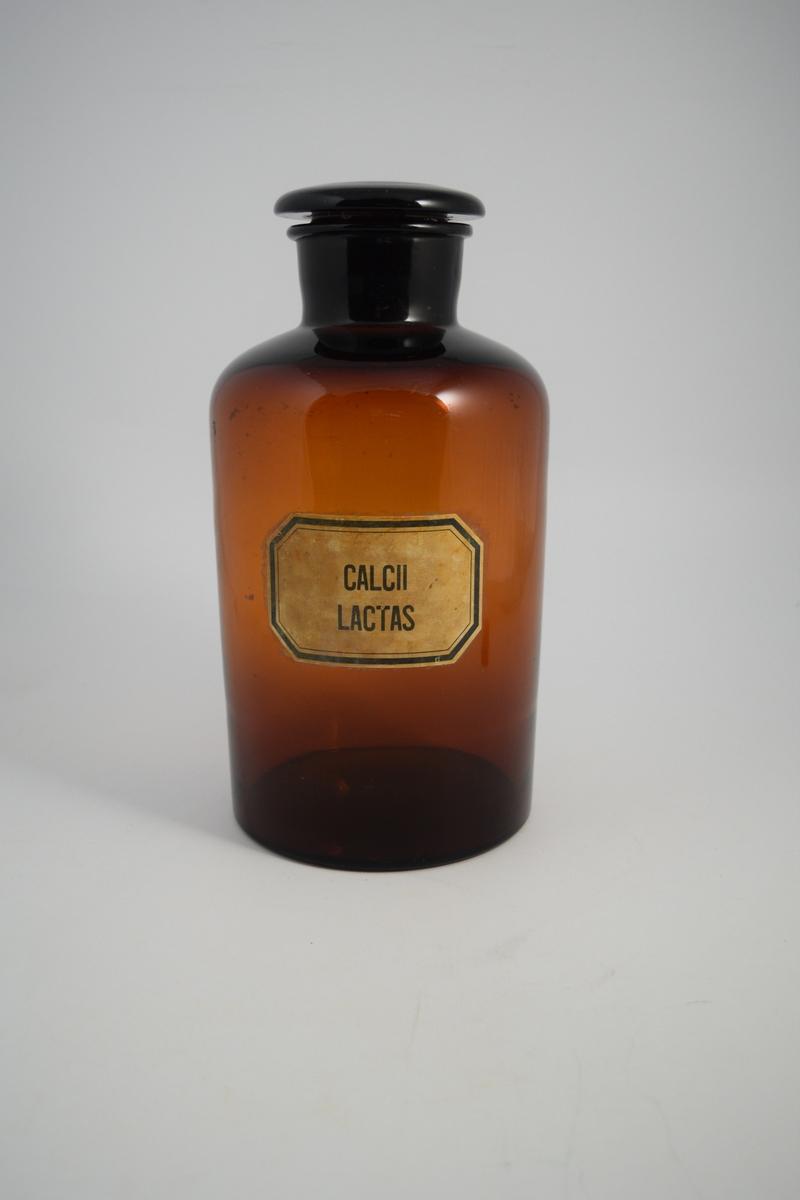 Brun glasskrukke med brun glasspropp, brukt til oppbevaring av pulver. Påført hvit etikett med sort skrift. Calcii lactas vil si melkesur kalk.