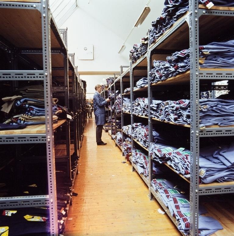 Mann mellom reolene i ferdiglageret for jeans i konfeksjonsfabrikken til Jonas Øglænd AS på Sandnes.