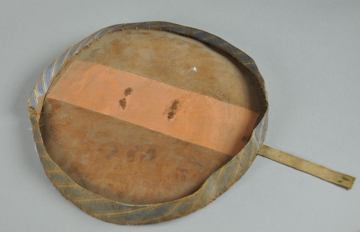 Lokk til hatteeske, av papp. Lokket er brunt med svart påskrift. Det er et hengslet håndtak av jern på midten av lokket. På langsidene er det bånd av tekstil for feste til esken.