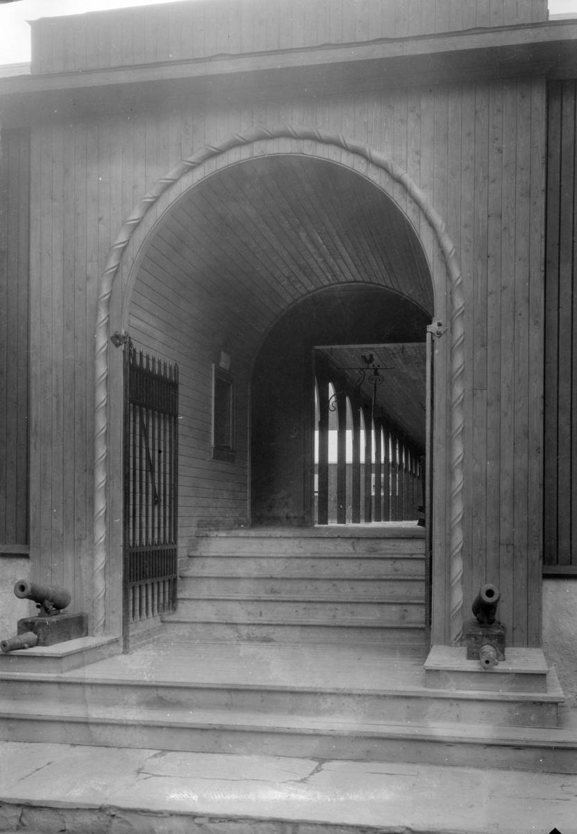 Inngangsparti med trapp. To små kanoner.