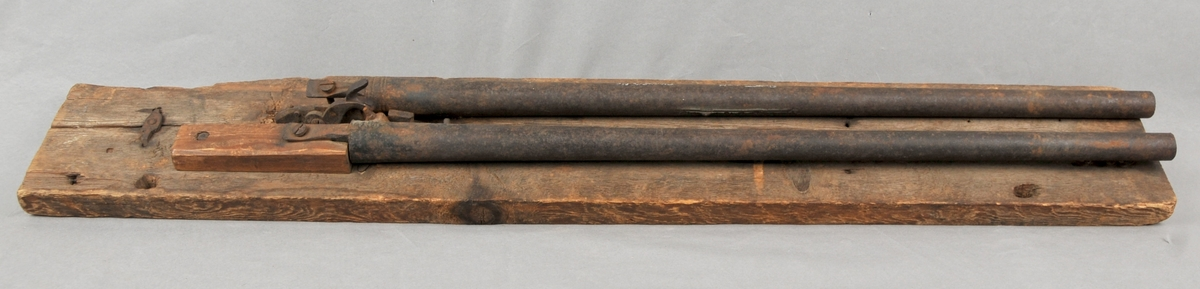 To børselaup liggjande på ei tjukk treplate. Dei er av jern og er bora. Begge er festa til treunderlaget med ein skruve som går gjennom eit lite trestykke og vidare ned i plata. Munnladning. Perkusjonslåssystem. Geværa har ein felles hane som står i samband med utløysar - og fjørmekanisme seks cm lenger framme på treplata.
