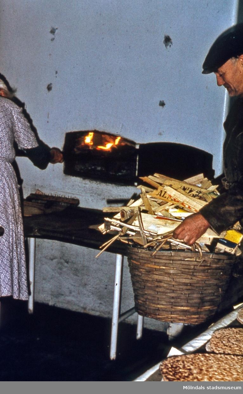 Gökegården 1 i Eklanda, Mölndal, år 1964. Valter Johansson bär in ved till bakstugan.