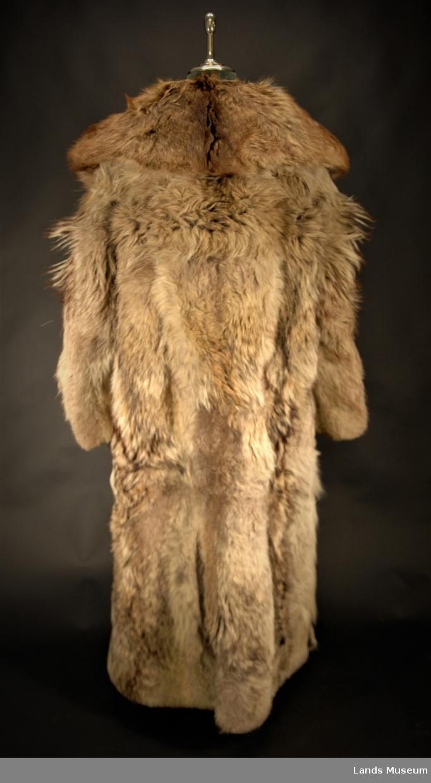 Herrepels med knapper på høyre side. Stor krage med beinskinn på undersiden. Navneskilt brodert: lengde 11 cm, bredde 7,5 cm. Foret med grå klede.