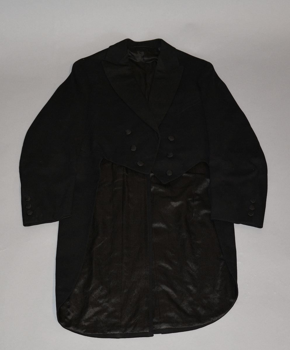 Livkjole med vest i sort ull. Slag i sort silkerips. En brystlomme på venstre side. Seks knapper i front. Tosømsermer med tre knapper på hvert erme. To knapper i ryggen ved splitten. Fôret med sort silke.