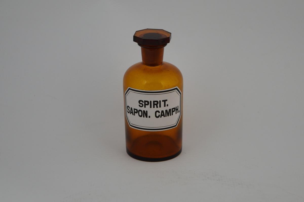 Brun glassflaske, smal hals, åttekantet glasspropp, slipt. Pålimt hvit etikett med sort skrift og sorte linjer langs kantene. Krukken ble brukt til oppbevaring av kamfersåpesprit.