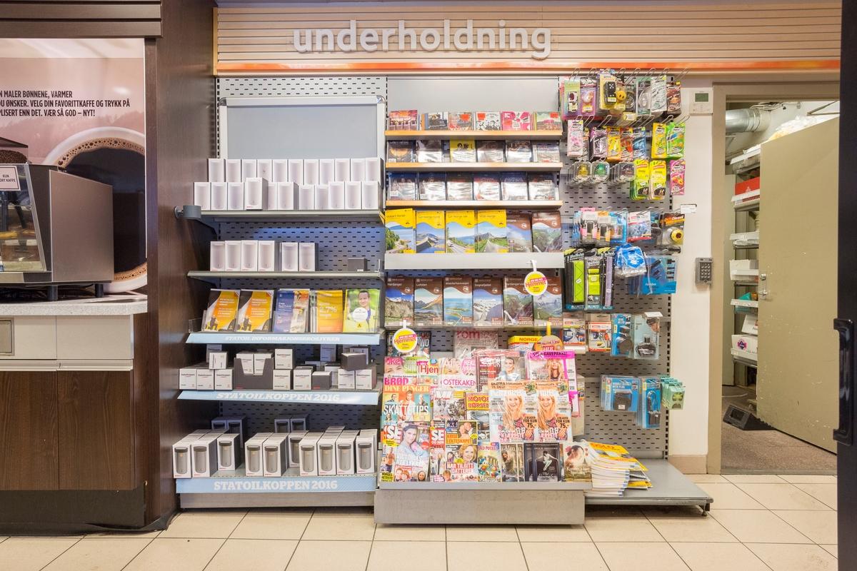Statoil Nadderud. Butikk interiør med hylleseksjon med Statoilkopper, ukeblad, veikart og elektriske artikler. Butikkskilt Underholdning.