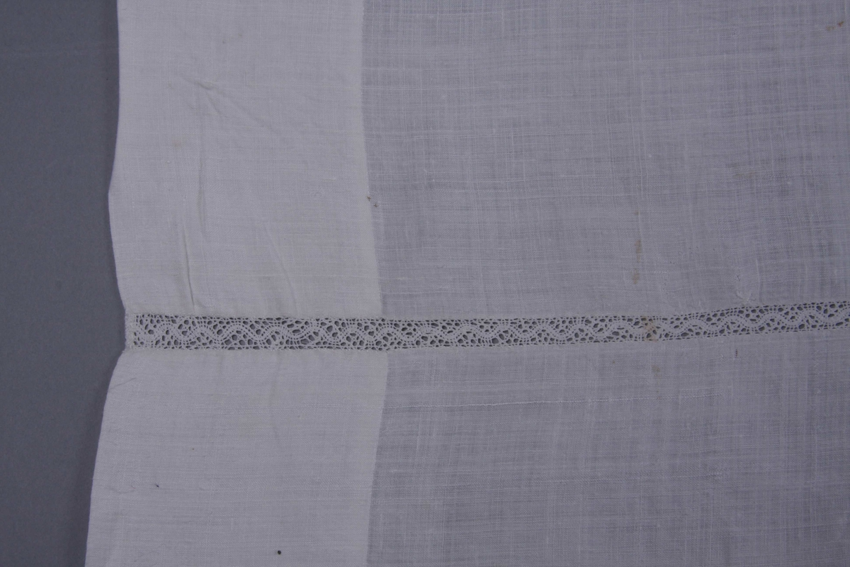 Hvit linlerret i tre bredder sydd sammen med en 1 cm. bred knipling med mønster av bølget bånd. 8 cm. bred fall på alle fire sider.