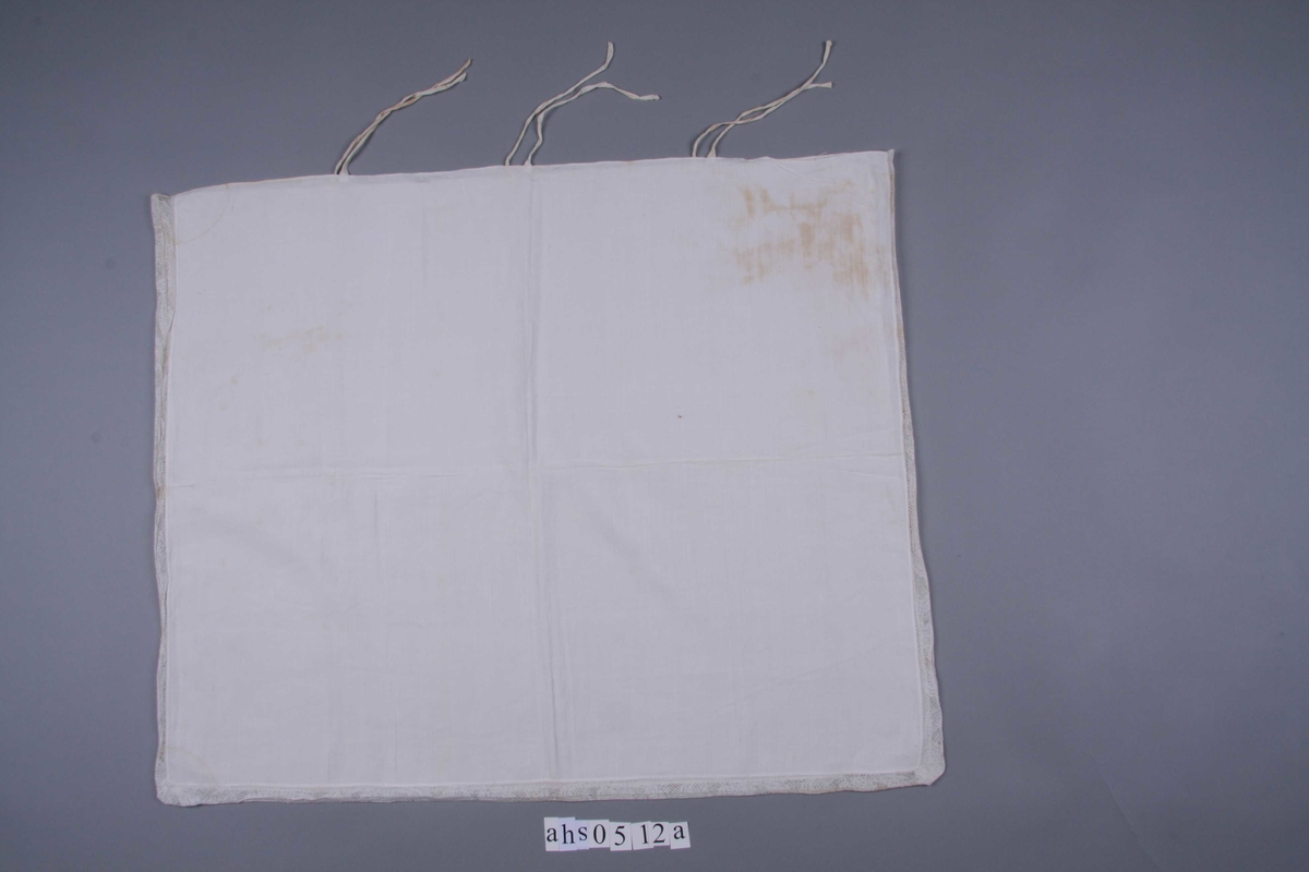 Hvit linlerret sydd sammen på tre sider med en 3,5 cm. bred knipling, meget fin med mønster av ren barokk blomsterranke. Smal fall på den fjerde siden. Med knytebånd.