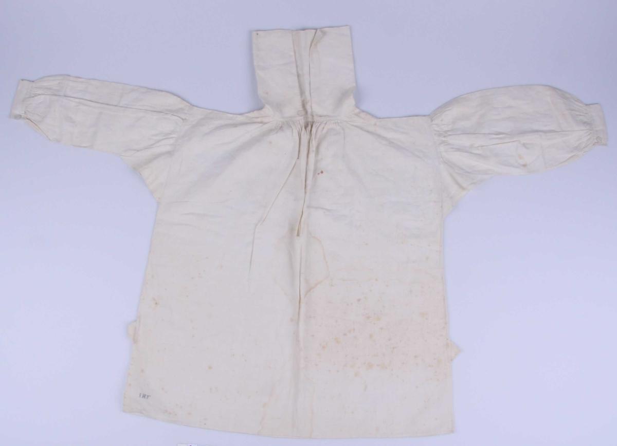 Av hvit lin, i ett stykke lagt dobbelt med søm i sidene, innfelt trekantet stykke, dobbelt, på skuldrene nærmest halsen og påsydd 3 cm. bred remse langs skulderen. Skjorten er rynket i halsen med 16 cm. høy krage av dobbelt stoff. Hvit possementsknapp og knapphull. Ermene er lagt i små folder øverst og har en innfelt firkant under armen. Nederst rynket til en 2,7 cm. bred linning pyntet med en rad attersting oppe og nede. Hvit possementsknapp og knapphull. Splitt i sidene med trekantforsterkning øverst. Smal fall nedentil, alt håndsydd.