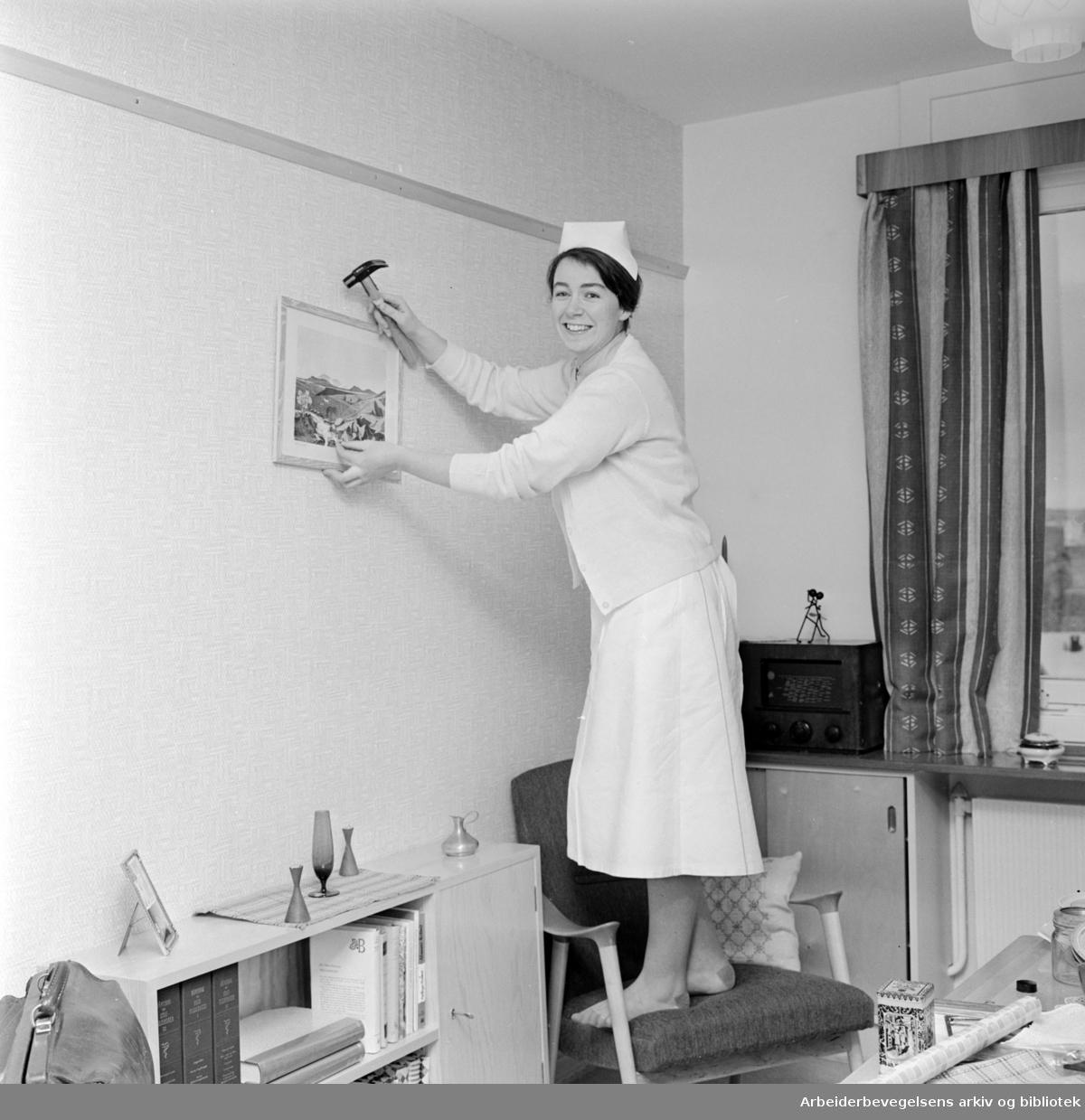 Ullevål Sykehus. Sykepleierske Ragna Rønhovde henger opp et bilde på veggen i oppholdsrommet. Desember 1961