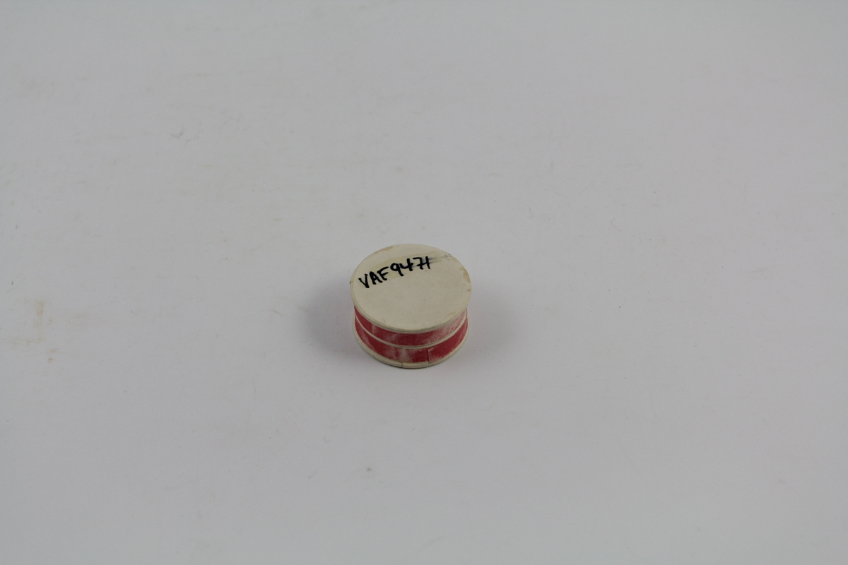 Sirkelformet eske med lokk. Rød farge. Brukt til oppbevaring/salg av piller eller pulver.