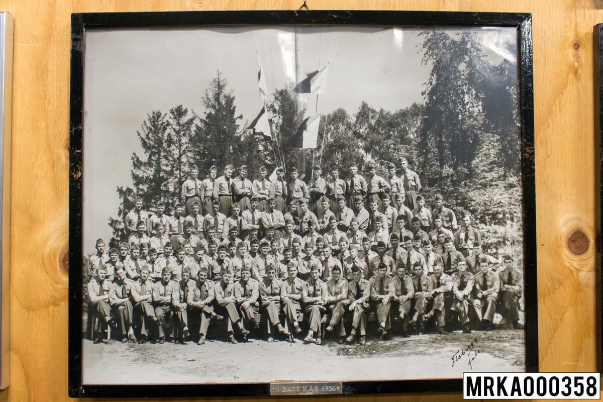 Fotografi taget på befäl och soldater som genomfört grundläggande soldatutbildning på 1:a Batteriet KA 2. Fotografiet taget på övre plan Gräsvik KA 2. Flobergs Foto 1956.