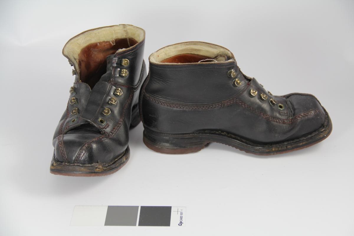 Et par sorte sko i lær. Kraftige og stive. Sydd med dekorsøm i rødt. Kraftig såle i gummi, brun under, med bølgemønster. 10 metallhemper på hver sko til å snøre skoen. Snøre mangler. Rester av tidligere fôr av ull i toppen av skoen.