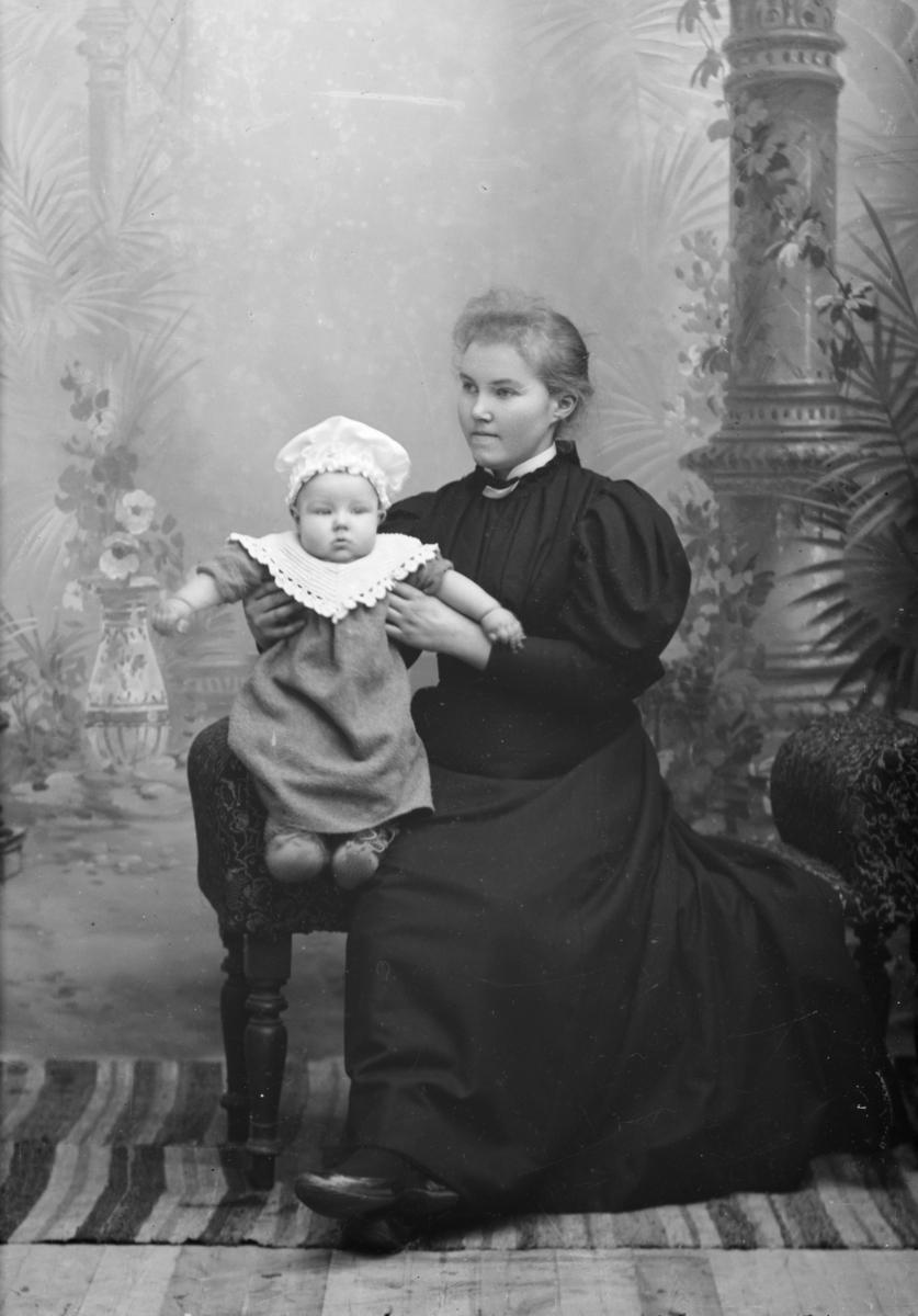 Sverre Lie på morens fang, helfigur. Fotograf Hans H. Lies familie.
