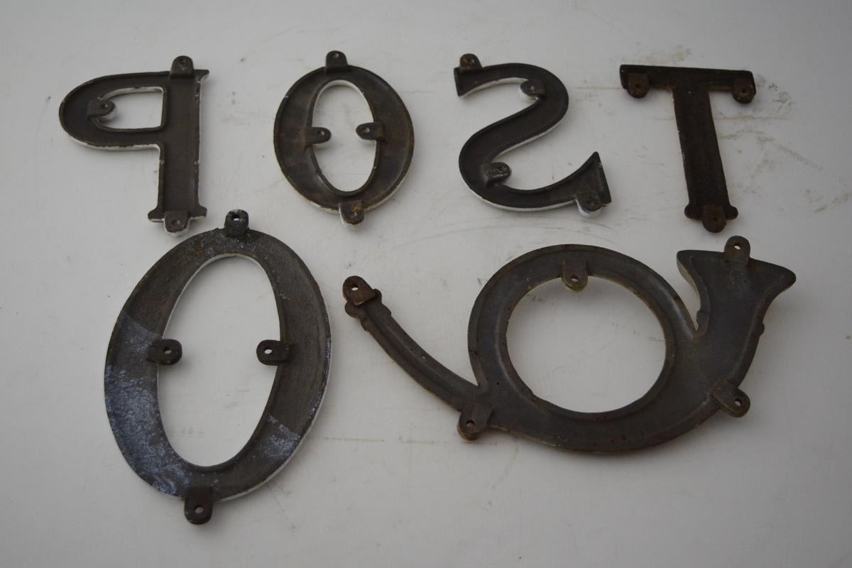 6 stk. hvite emaljeskilt til lokomotivvogner. Bokstaver og et posthorn montert sammen, danner teksten: POST O. Usikker plassering av den store O-en. Hull til oppheng. T-en er malt hvit.