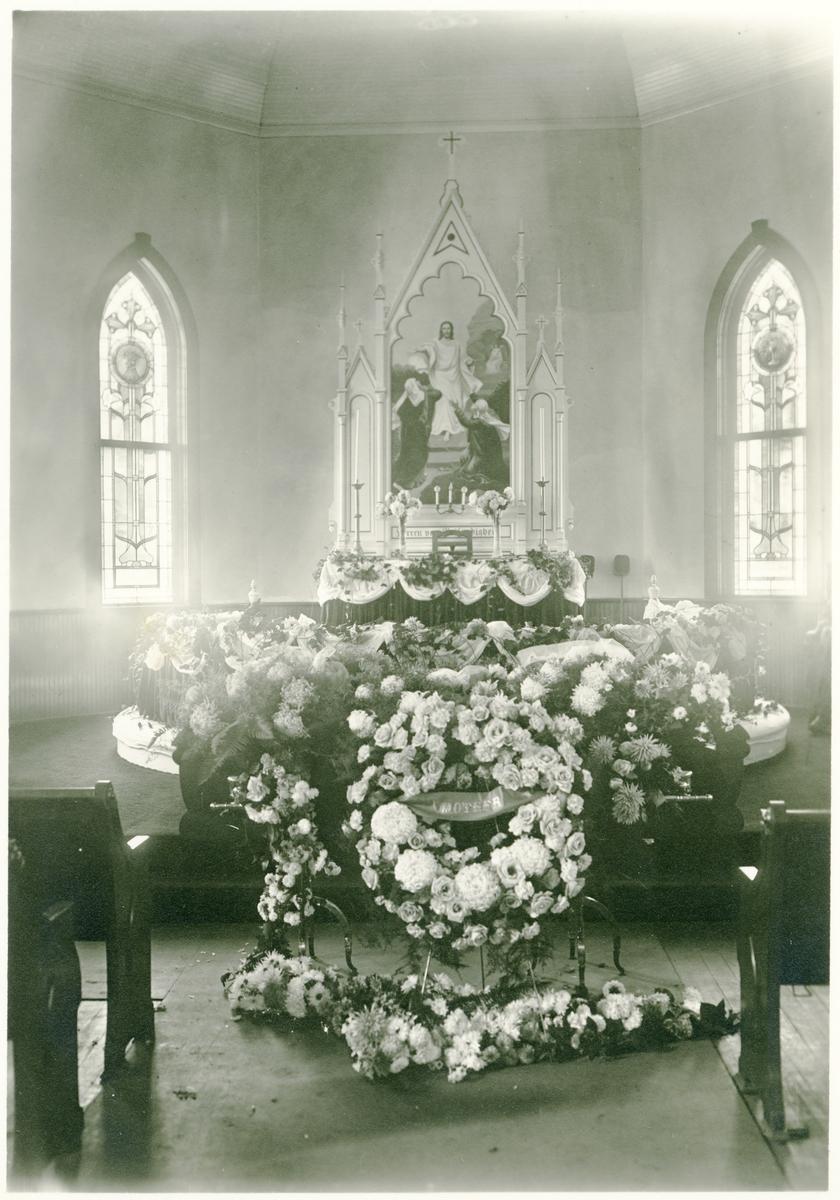 """Begravelse. Mye blomster rundt kista. """"Mother"""" står skrevet på et silkeband over en krans."""
