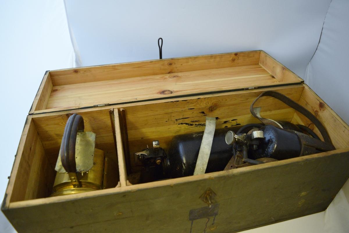 Trekasse med AGA-håndlykt lykt i messing(?) med trehåndtak. To gassbeholdere for AGA-gass (en liten og en stor). Arbeidslys for redskapsvogn 432 - merket med mørkeblått.