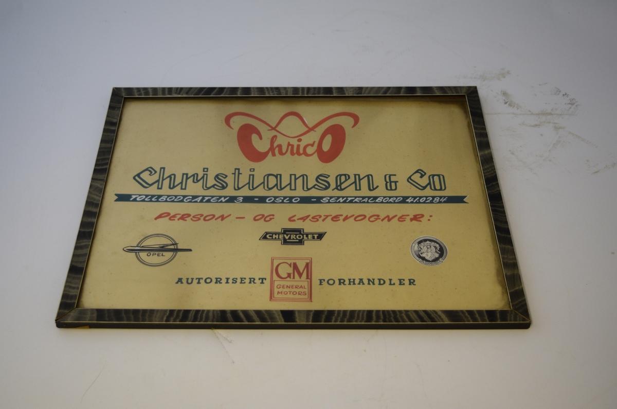 Reklameplakat i treramme med glass. Trekantet metalloppheng festet til øverste rammelist. Bakplate av papp, festet med metallstifter.